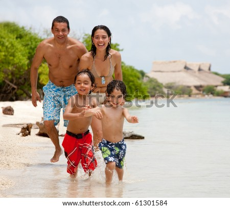 Happy family on holidays playing at the beach - stock photo
