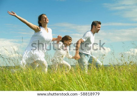 Happy family on meadow - stock photo