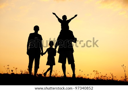 Happy family on meadow at summer sunset - stock photo