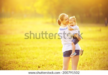 happy family on nature outdoors mother and baby daughter on the green meadow  - stock photo