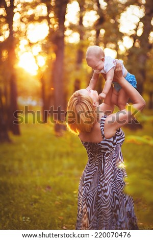 happy family on nature outdoors mother and baby daughter on the green meadow. Young mother with child outside on a summer day - stock photo