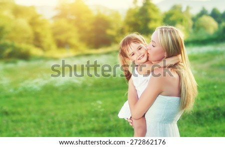 happy family on nature outdoors mother kissing little daughter on the green meadow - stock photo