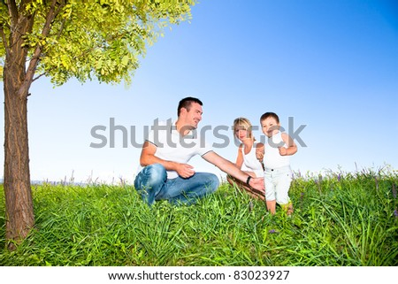 Happy family on picnic in park under tree - stock photo