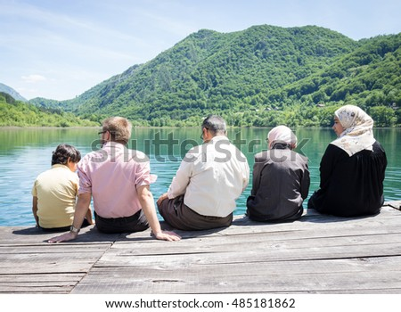 Happy family on summer vacation having fun and happy time next to the mountain lake