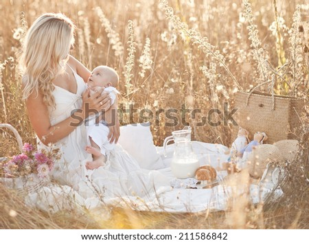 Happy family on sunset. Mother in white dress with baby in nature - stock photo