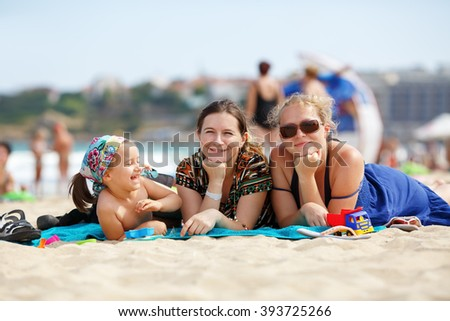 Happy family on the beach. Two pretty young women and a little girl child is lying on the beach. Selective focus. - stock photo