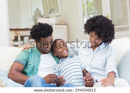 Happy family on the couch at home in the living room - stock photo