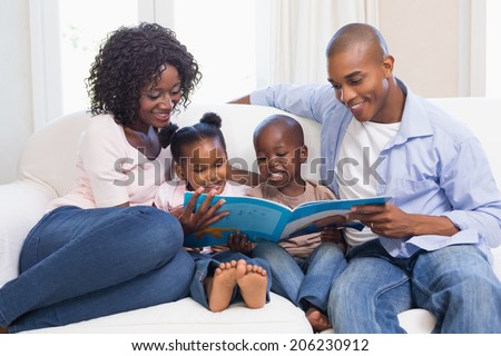 Happy family on the couch reading storybook at home in the living room - stock photo