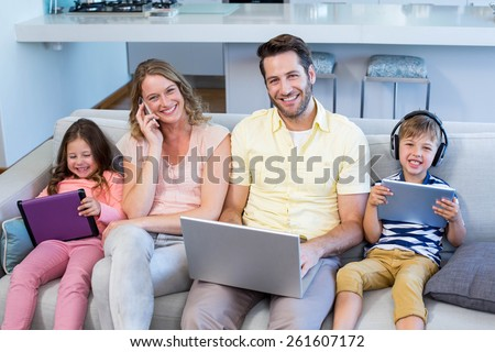 Happy family on the couch together using devices at home in the living room