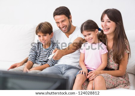 Happy family on the couch watching television together - stock photo