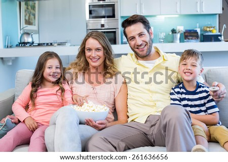 Happy family on the couch watching tv at home in the living room - stock photo