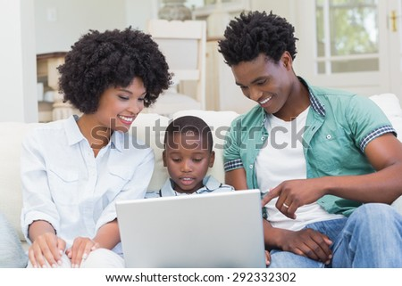 Happy family on the couch with laptop at home in the living room