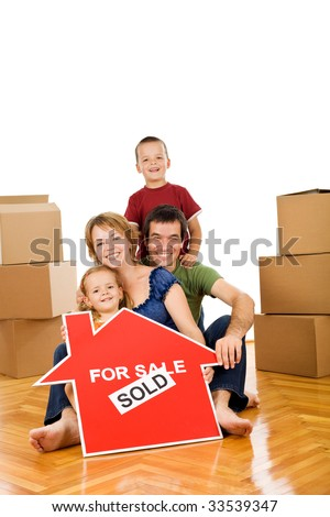 Happy family on the floor of their new home with cardboard boxes and house sold sign - isolated - stock photo
