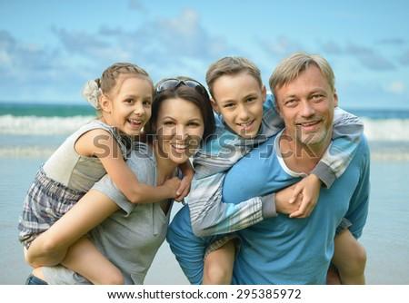 Happy family  on the sea beach background - stock photo