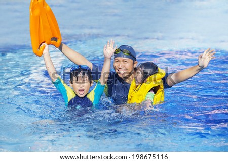 Happy family on the swimming pool together - stock photo