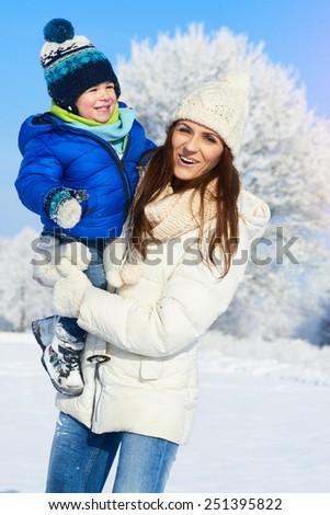 Happy family on the walk in sunny, snowy day - winter holidays - stock photo