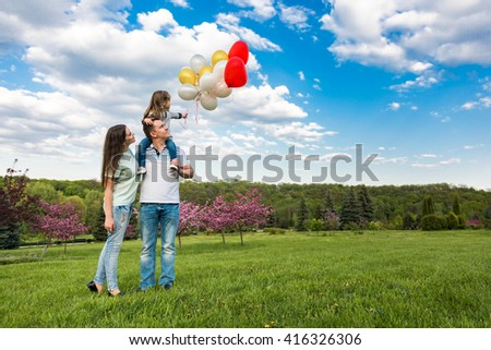 Happy family on the weekend, daughter playing with the balloons - stock photo