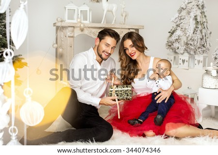Happy Family opening a Christmas Present. Happy family in Christmas Time - stock photo