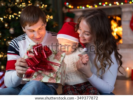 Happy family opening gift on Christmas and New Year
