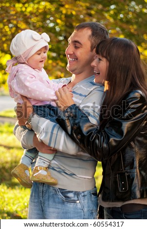 Happy family outdoor - mother, father and dauther are smiling - stock photo
