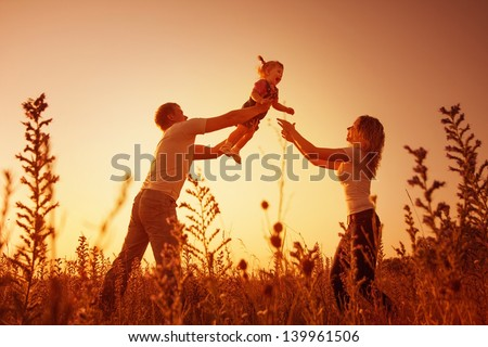 happy family outdoor, silhouettes on sunset - stock photo