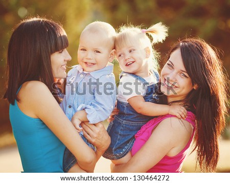 happy family outdoors in a park. Two women and two children smiling - stock photo