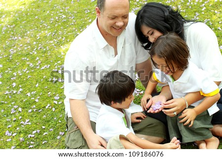 Happy family outdoors in the park - stock photo