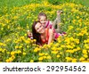 Happy family outdoors  mum and kid girl child among yellow flowers dandelions - stock photo