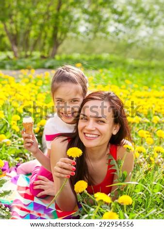Happy family outdoors  mum and kid girl child among yellow flowers dandelions - stock photo