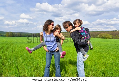 Happy family outdoors. Parents giving their kids piggyback ride