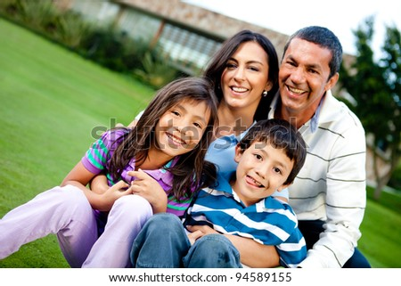 Happy family outdoors with a house at the background - stock photo