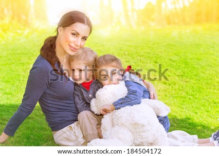 Happy family outdoors, young mother with two precious child sitting of fresh green grass field, summer vacation, love and togetherness concept