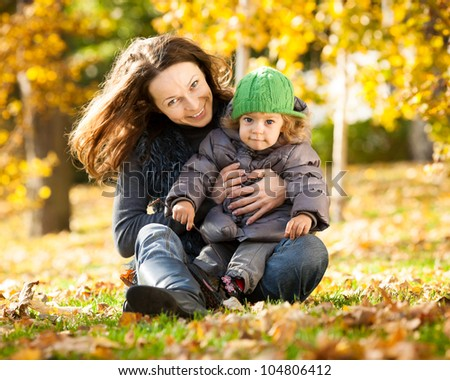 Happy family playing against blurred yellow leaves background in autumn park