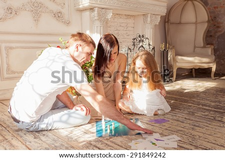 Happy family playing board game  in their living room - stock photo
