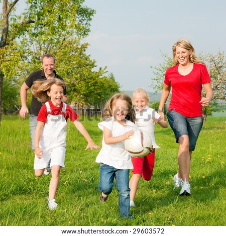 Happy family playing football, one child has grabbed the ball and is being chased by the others - stock photo