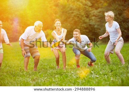 Happy family playing frisbee together in the garden in summer - stock photo