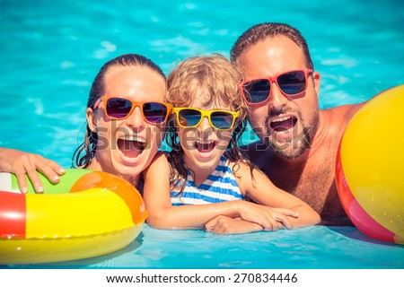 Happy family playing in swimming pool. Summer vacation concept - stock photo