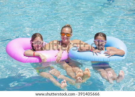 Happy Family playing on inflatable tubes in a swimming pool on a sunny day - stock photo