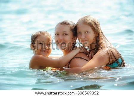 Happy family playing on sea - stock photo