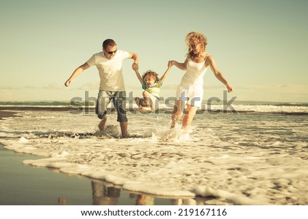 Happy family playing on the beach at the day time. Concept of friendly family. - stock photo