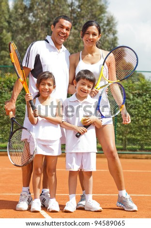 Happy family playing tennis holding rackets and smiling