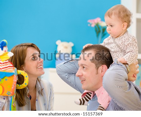 Happy family playing together: mother, father and 1 year old baby girl at children's room, smiling. Toys are officially property released.