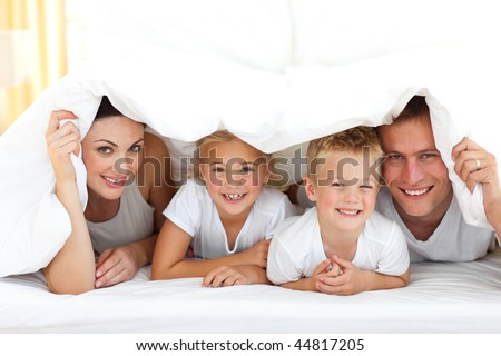 Happy family playing together on a bed at home - stock photo