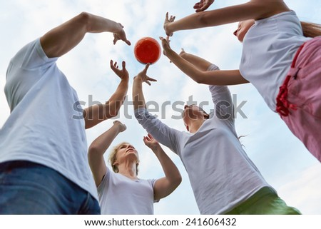 Happy family playing with a ball together outdoors - stock photo