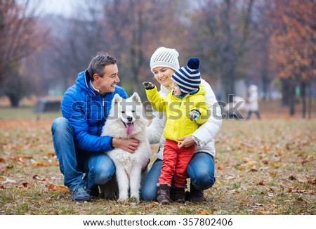 Happy family playing with a samoyed dog in autumn park - stock photo