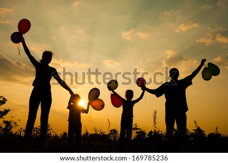 Happy  family playing with balloons on the  road in the  sunset time. Evening party on the nature