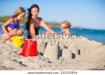 Happy family playing with beach toys during tropical vacation - stock photo