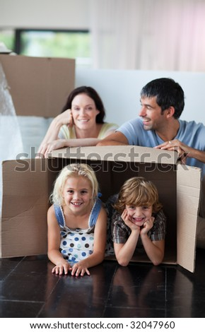 Happy family playing with boxes after moving house