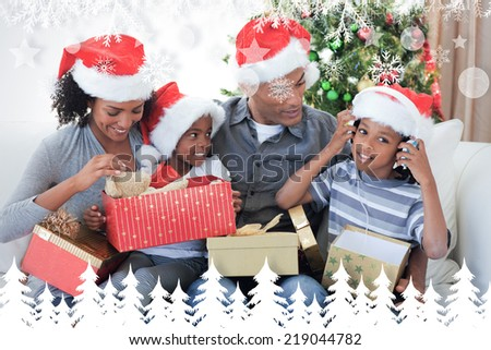 Happy family playing with Christmas presents against fir tree forest and snowflakes - stock photo