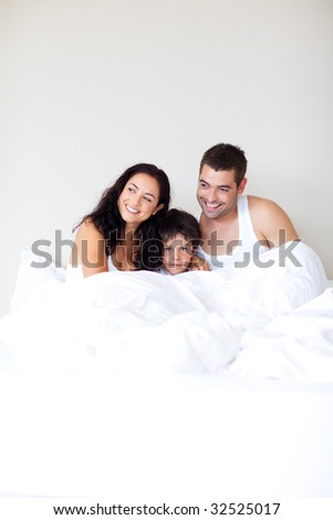 Happy family playing with his son in bed with copy-space - stock photo